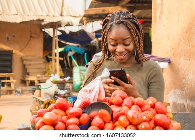 young african woman in a local african market viewing content on her phone and looking surprised