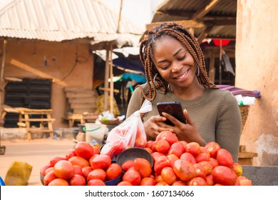 young african woman in a local african market viewing content on her phone smiling