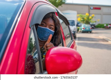 Young African woman in mask sitting in a car,wearing homemade mask and giving a thumbs up through vehicle window