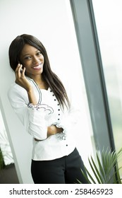 Young african woman in the office with mobile phone