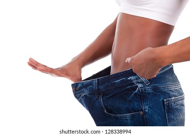 Young african woman in old jeans pant after losing weight. Isolated on white background.