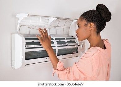 Young African Woman Opening Air Conditioner At Home