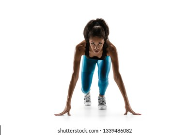 Young african woman preparing to start run isolated on white studio background. One female runner or jogger. Silhouette of jogging athlete.