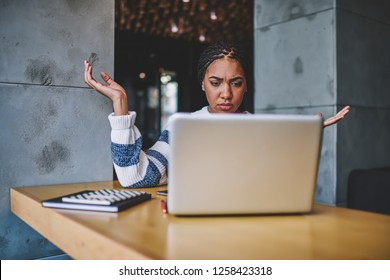 Young african woman reading message about problem with installing application on laptop computer feeling confused and trying soling trouble, puzzled female have video conference with colleague
