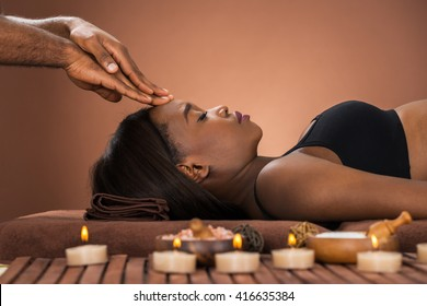 Young African Woman Receiving Forehead Massage At Spa