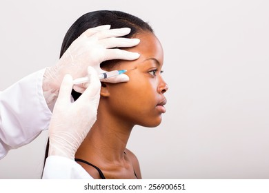 young african woman receiving plastic surgery injection on her face