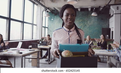 Young african woman recently hired for corporate job comes into new office. Female holds box with personal belongings.