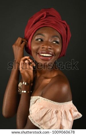Young African woman with red turban smiling