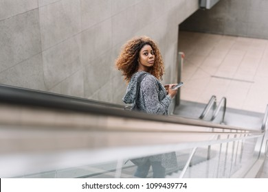 Young African woman riding a subway escalator looking back over her shoulder at the camera with a quizzical look