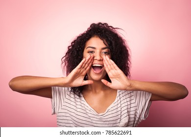 Young african woman shouting on pink background