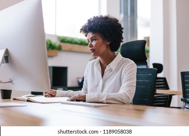 Young african woman sitting at her desk looking at computer screen and making notes in a book. Female entrepreneur working in her office.
