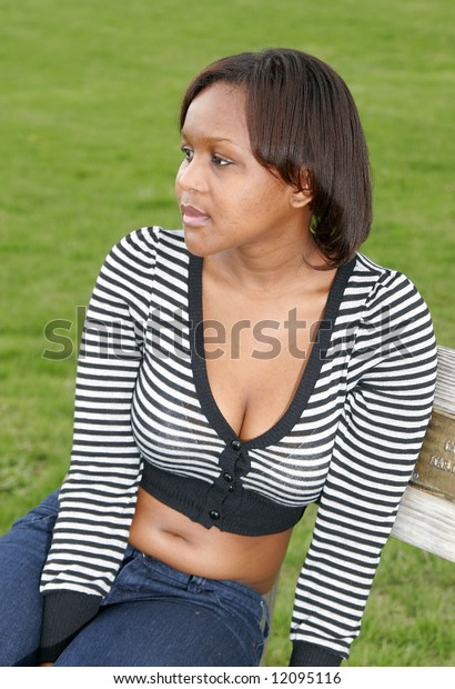 a young African woman sitting on a bench looking off to the side