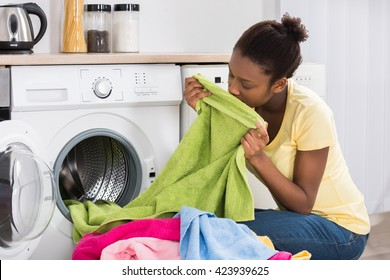 Young African Woman Smelling Clothes After Washing At Home
