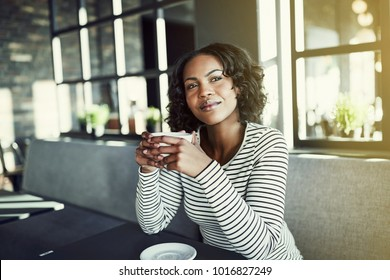 Young African woman smiling and looking deep in thought sitting alone at a table in a cafe enjoying a fresh cup of coffee