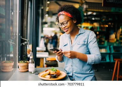 Young African woman smiling while sitting alone at a counter in a bistro taking photos of her meal with her smartphone