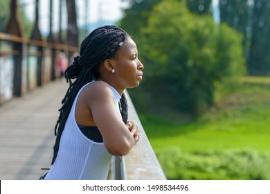 Young African woman standing leaning on the wooden railing staring off a bridge deep in thought in a profile view