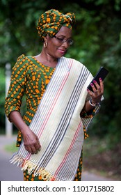 young african woman standing in loincloth and glasses looking at mobile phone while smiling.