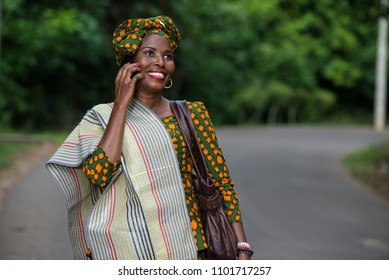 young african woman standing in traditional clothes on mobile phone smiling.