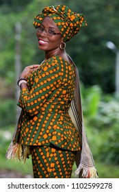 young african woman standing in traditional outfit and glasses looking in profile while smiling.