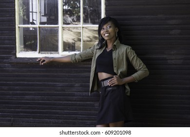 A young African woman stands in front of an old wood slatted house