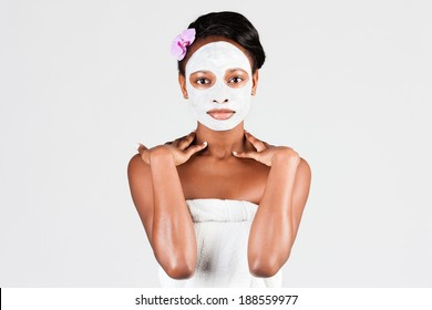 Young African woman in Studio doing body care with refreshing facial mask for young and beautiful skin and relaxation