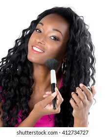 Young African woman in Studio doing body care and applying makeup, powder and rouge with a brush for young and beautiful skin