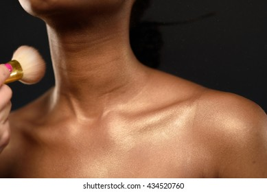Young African woman in Studio doing body care and applying makeup, powder with a brush for beautiful skin