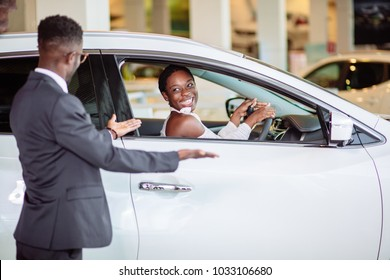 young african woman surprised by new car, gift for my beautiful wife