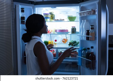 Young African Woman Taking Out Bottle From Open Refrigerator