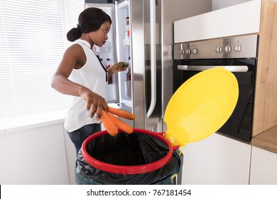 Young African Woman Throwing Carrot In Trash Bin