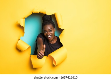 Young african woman with thumbs up posing from yellow hole