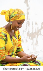 Young African woman in traditional clothes typing a message on her phone