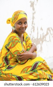 Young African woman in traditional clothes sitting outdoors and looking at camera