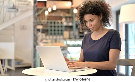 Young African Woman using Laptop in Cafe
