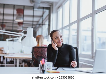Young african woman using mobile phone while at work. Female executive in conversation on a mobile phone while sitting at her desk.