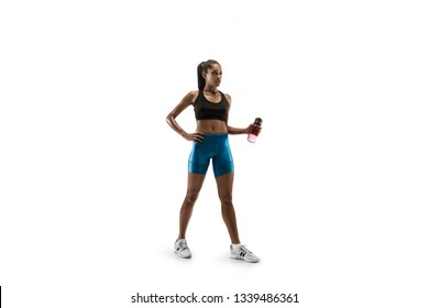 Young african woman with water before run isolated on white studio background. One female runner or jogger. Silhouette of athlete.