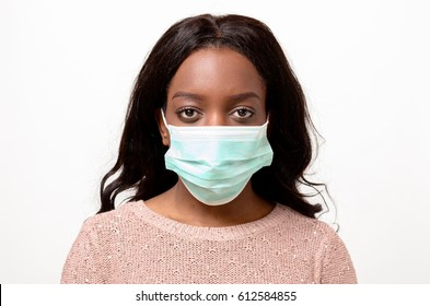 Young African woman wearing a surgical face mask covering the lower half of her face in a medical and healthcare concept looking at the camera with a calm serious expression