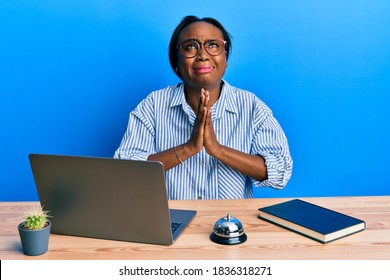 Young african woman working at hotel reception using laptop begging and praying with hands together with hope expression on face very emotional and worried. begging.