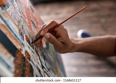 Young African-American artist painting picture in workshop, closeup