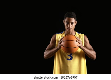 Young African-American basketball player on dark background