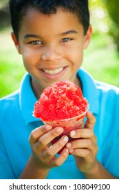 A young African-American boy holds a snow cone as he smiles at the camera.