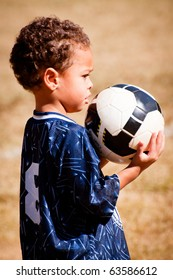 Young African-American boy with soccer ball before game.