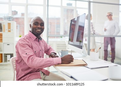 Young African-american businessman looking at camera while making working notes