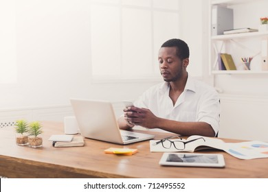 Young african-american businessman in office, texting on phone while working on laptop