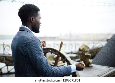 Young African-american businessman standing by sailing wheel and turning it while leading large ship
