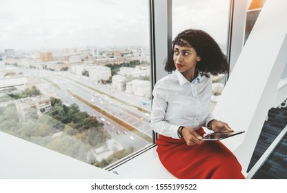 A young African-American businesswoman with a digital tablet sitting on a white surface near the window of an office skyscraper; a charming biracial female with a tablet pc in a business high-rise