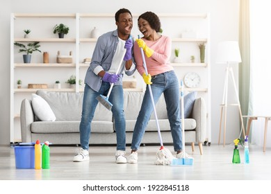Young african-american couple cleaning home, playing with mop and broom, having fun in living room, full length shot, copy space. Happy black family singing and dancing while cleaning apartment