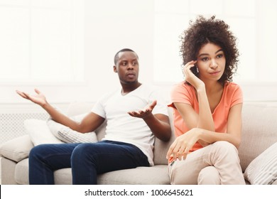 Young african-american couple quarreling at home, woman offended. Family relationship difficulties concept