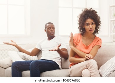Young african-american couple quarreling at home, woman offended. Family relationship difficulties concept, copy space