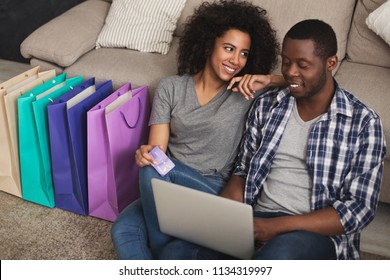 Young african-american couple shopping online on laptop, sitting at home with colorful bags, copy space